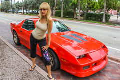 Woman and sports car. Attractive blond woman stood next to a red sports car in Miami, Florida, U.S.A Stock Photography