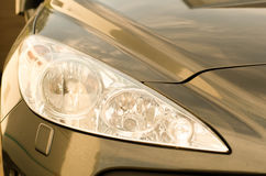 Sports car headlight gold. A close-up picture of headlights on a golden sports car Royalty Free Stock Image