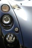 Sports car headlights in black. Sports car headlights and bonnet  shot reflecting the sunshine Stock Image