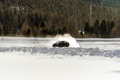 A sports car on the ice speeding and burning tires in winter in a snowy ice piste.  Stock Image