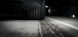 Sports car leaving wet tire prints Stock Photo
