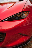 Sports car MX 5 detail. Red MX 5 sports car, 2016 Recaro model,  with closeup detail of offside right front wing and headlight Royalty Free Stock Photo
