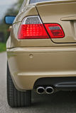 Sports car rear detail. Golden sports car with wide tires and LED lights stock photo