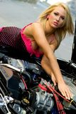 Sports Car and Sexy Girl Blonde. Sexy Girl Blonde fashion model in cute dress checking out the engine in a black sports car Royalty Free Stock Images