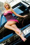 Sports Car Sexy Girl Blonde. Sexy Girl Blonde fashion model in sexy dress laying on a black sports car Royalty Free Stock Photo