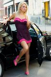 Sports Car Sexy Girl Blonde. Sexy Girl Blonde fashion model in sexy dress standing next to a black sports car Stock Photography