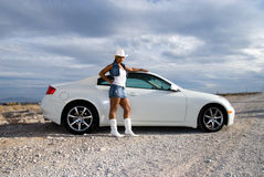 Sports car and sexy woman. Beautiful African American woman wearing a short denim skirt and white cowboy boots standing by a car in the desert, as a storm is Stock Images