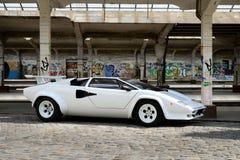 Sports car. Sleek white modern sports car parked on cobblestones Stock Photos