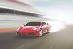 Sports car speeding on a track. Panning shot of a beautiful red car speeding on a highway with motion blur Royalty Free Stock Images