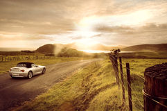Sports Car Sunrise. Modern silver convertible sports car driving into a dramatic sunset / sunrise on unsealed road near farmland and wire fence Royalty Free Stock Photography