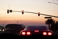 Sports car sunset. A sports car waiting at a red light, with tail lights glowing at sunset near the beach Royalty Free Stock Photography