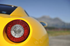 Sports car tail light. Closeup of tail light on yellow modern sports car with road and mountains in background Stock Image