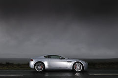 Sports car under stormy sky. A profile of a silver, sporty, Aston Martin V8 Vantage under a dark, stormy sky Stock Photography