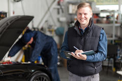 Sports car in a workshop. Sports car in a service workshop - mechanic inspecting the vehicle Royalty Free Stock Image