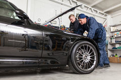 Sports car in a workshop. Sports car in a service workshop - two mechanics inspecting the engine Royalty Free Stock Photos
