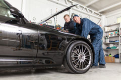 Sports car in a workshop. Sports car in a service workshop - two mechanics inspecting the engine Stock Photos