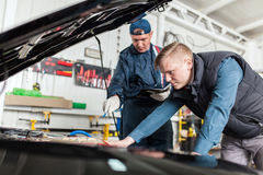 Sports car in a workshop. Sports car in a service workshop - two mechanics inspecting the engine Stock Image