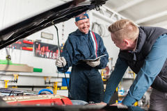 Sports car in a workshop. Sports car in a service workshop - two mechanics inspecting the engine Royalty Free Stock Image