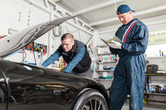 Sports car in a workshop. Sports car in a service workshop - two mechanics inspecting the engine Stock Images