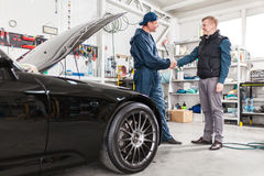 Sports car in a workshop. Sports car in a service workshop - two mechanics inspecting the engine Royalty Free Stock Images