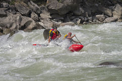 Sports catamaran  in the  rapids. CHUYA RIVER, RUSSIA - AUGUST 5, 2014. Sports catamaran moving away from a collision with a stone in a difficult rapids. River Stock Photos