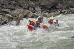 Sports catamaran  in the  rapids. CHUYA RIVER, RUSSIA - AUGUST 5, 2014: Sports catamaran overcomes difficult place in the  rapids. River Chuya, Altai. Tourists Royalty Free Stock Photos