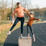 Sports cheerful family, healthy lifestyle, spring portrait of mother and little daughter having fun and running at the stadium.  stock photo