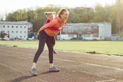 Sports cheerful family, healthy lifestyle, spring portrait of mother and little daughter having fun and running at the stadium.  stock image