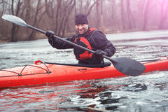Sports cheerful man in kayak. Man kayak is on a frozen river Stock Photos
