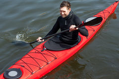 Sports cheerful man in red kayak Royalty Free Stock Image