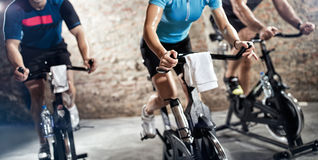 Sports clothing people riding exercise bikes. Cardio fitness class Stock Photography