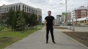 A sports coach stands in the middle of a city street. Confident posture and serious look of a man. City street on the background stock video footage