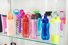 Sports colored plastic bottles for drinking water in shop Royalty Free Stock Photos