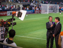 Sports commentary concept. Commentator speaking next to soccer pitch Stock Photos
