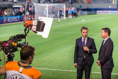 Sports commentary concept. Commentator standing next to soccer Stock Images