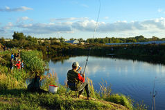 Sports competitions on fishing on catching of a carp and a sturgeon, fishermen on lake Royalty Free Stock Images