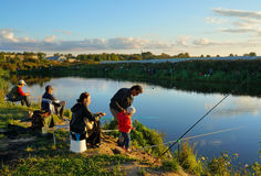 Sports competitions on fishing on catching of a carp and a sturgeon, fishermen on lake Stock Photo