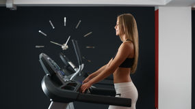 Sports concept. Girl trains on background of clock Stock Image