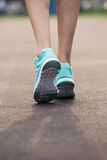 Sports concept. Runner woman feet running on road closeup on shoe. Female fitness model sunrise jog workout. Sports healthy lifestyle concept Stock Photography