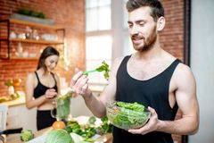 Sports couple eating healthy vegetarian food on the kitchen. Young sports couple having snack with healthy salad and green smoothie on the kitchen at home stock images