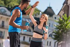 Sports couple giving highfive. Athletic sports couple giving highfive in city at daytime Royalty Free Stock Image