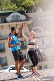 Sports couple giving highfive. Happy sportswoman and sportsman giving highfive in city at daytime Stock Photo