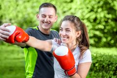 Sports couple in the park. Young sports couple training to box in the park Stock Image