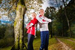 Sports d'aînés s'exerçant sur un chemin forestier Image libre de droits