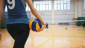 Sports for disabled people. A young woman trainer walks to her ward holding a volleyball ball and sit down on the floor