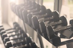 Black dumbbell set. Close up many metal dumbbells on rack in sport fitness center , Weight Training Equipment concept. royalty free stock image