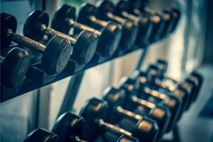 Black dumbbell set. Close up many metal dumbbells on rack in sport fitness center , Weight Training Equipment concept. royalty free stock images