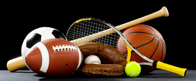 Sports Equipment. A variety of sports equipment on a black background including an american football, a soccer ball, a baseball, a baseball bat, a tennis raquet