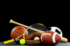 Sports Equipment. A variety of sports equipment on a black background including an american football, a soccer ball, a baseball, a baseball bat, a tennis raquet Stock Images