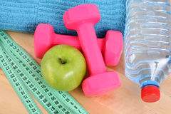 Sports equipment. Dumbbells water and green apple Royalty Free Stock Image